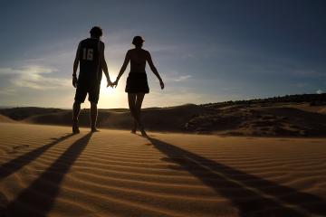 Saving Money for Travel: Couple holding hands in the desert