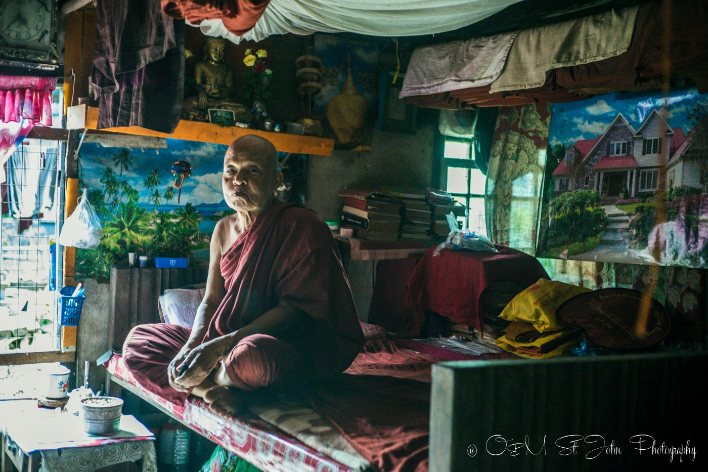 Older Burmese monk inside his living quarters in a monastery in Yangon. Myanmar