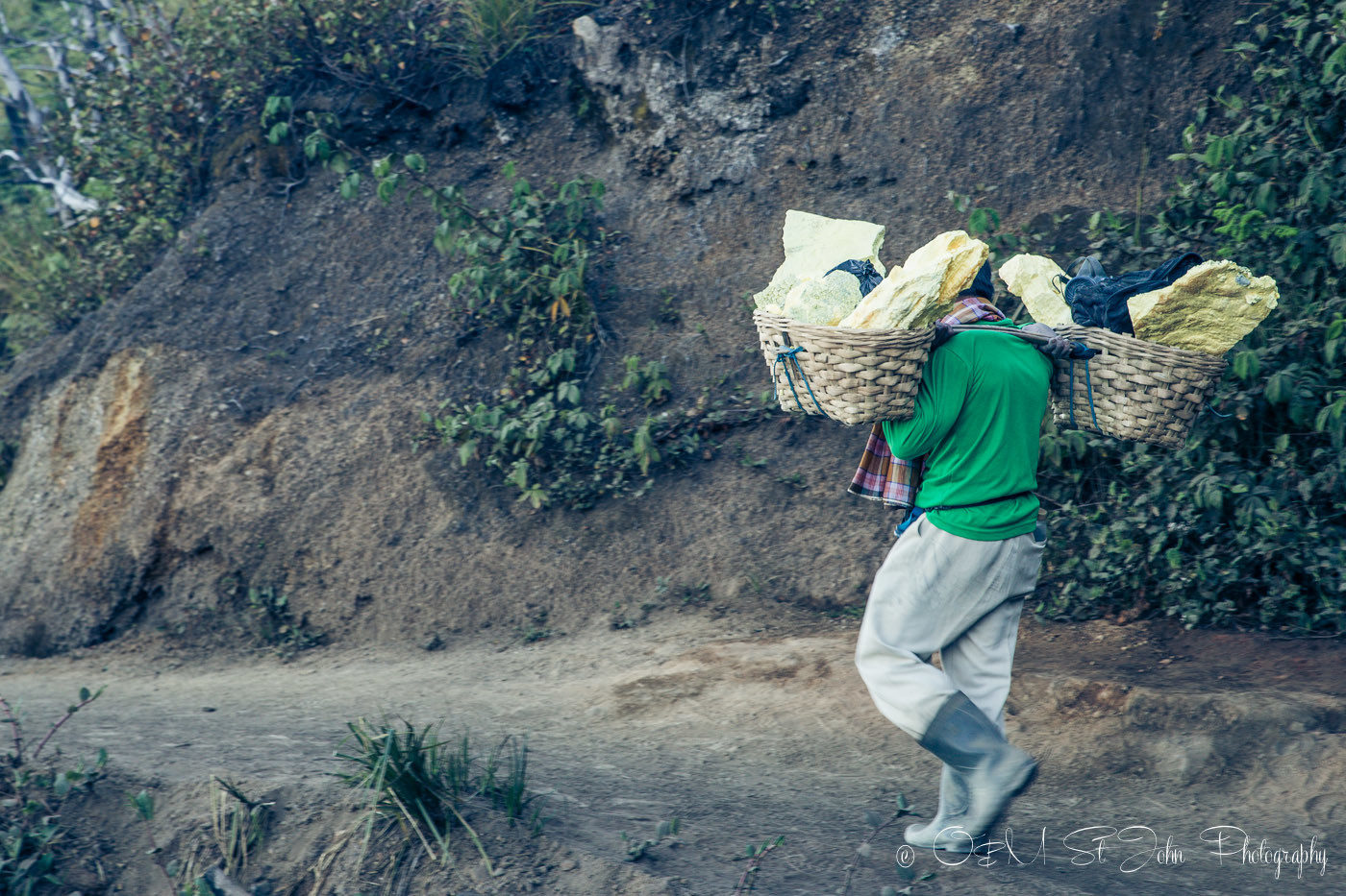 Sulfur miner making his way down with a load of sulfur. Ijen Crater. East Java. Indonesia