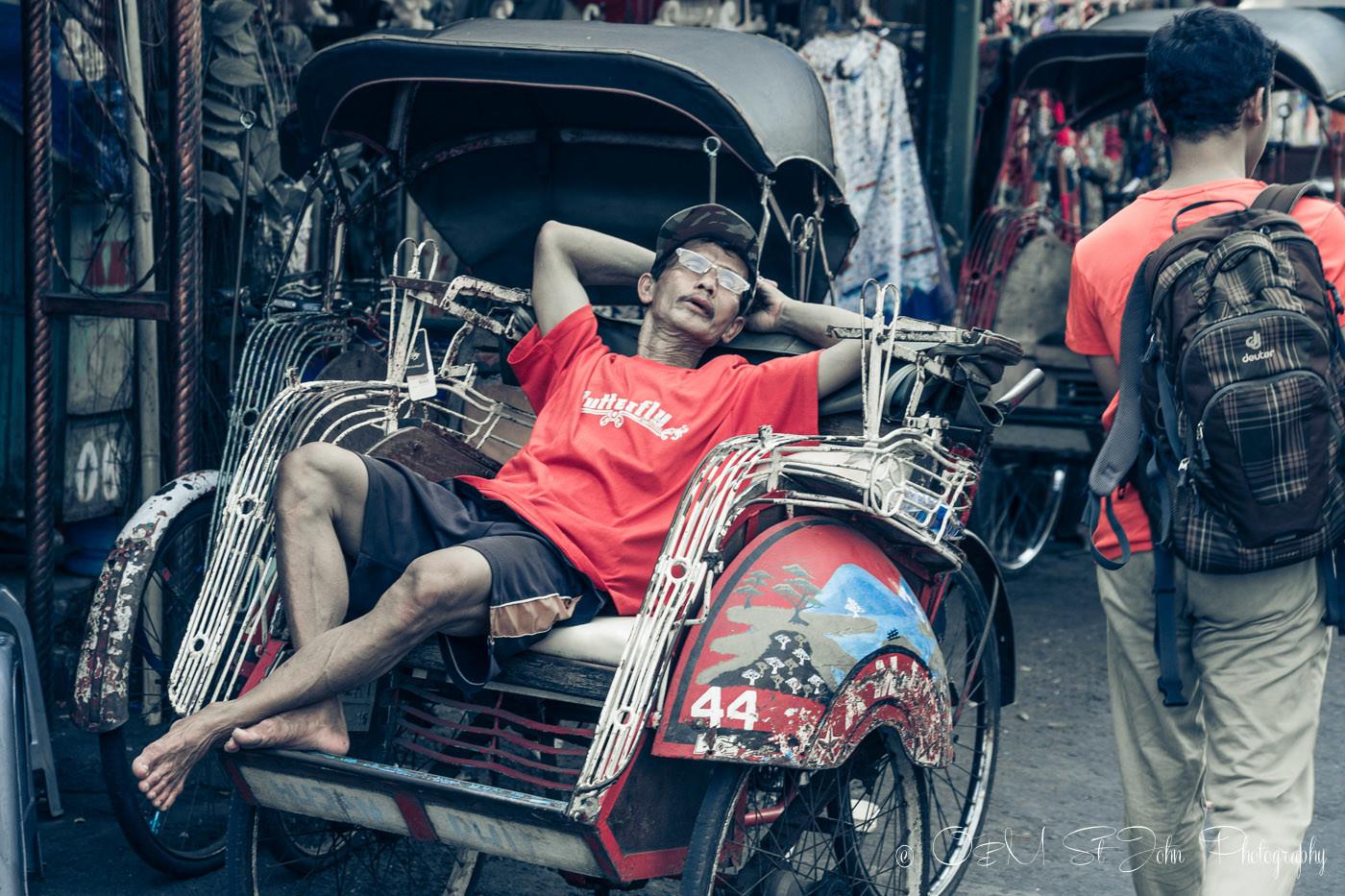 Becak driver taking a break on Jalan Malioboro before taking visitors on yogyakarta tour