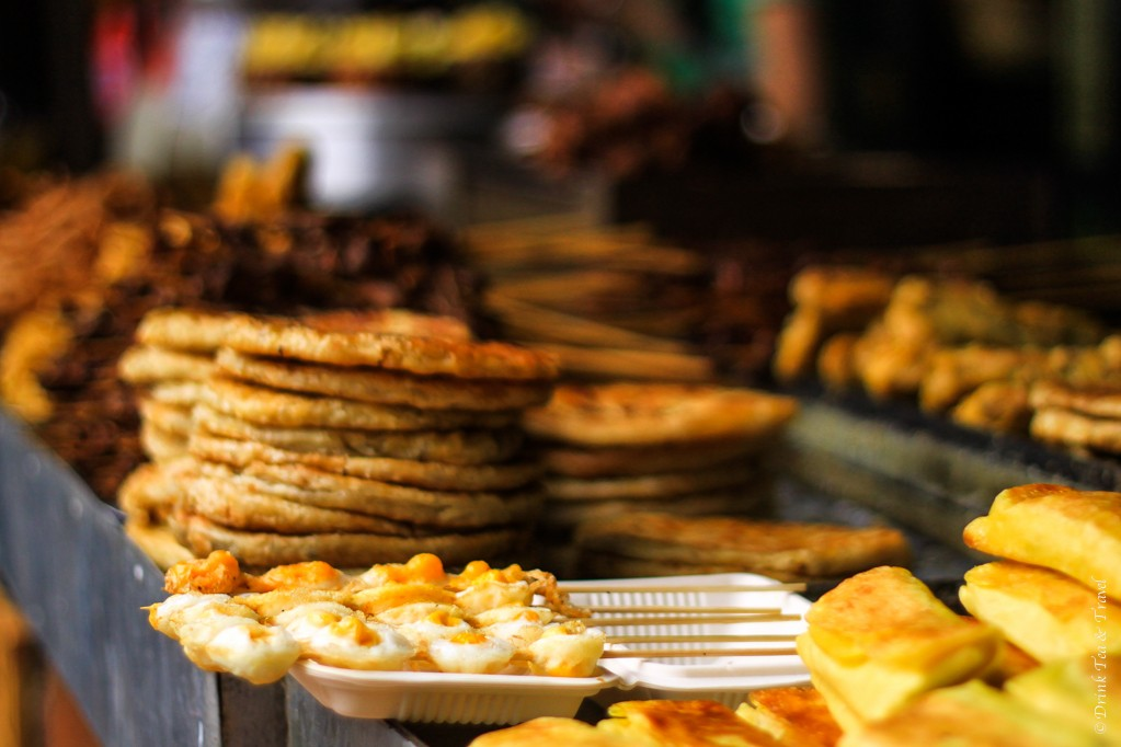 Variety of snacks on sale. On the left is a stack of Lijiang baba (pancakes). Lijiang, China
