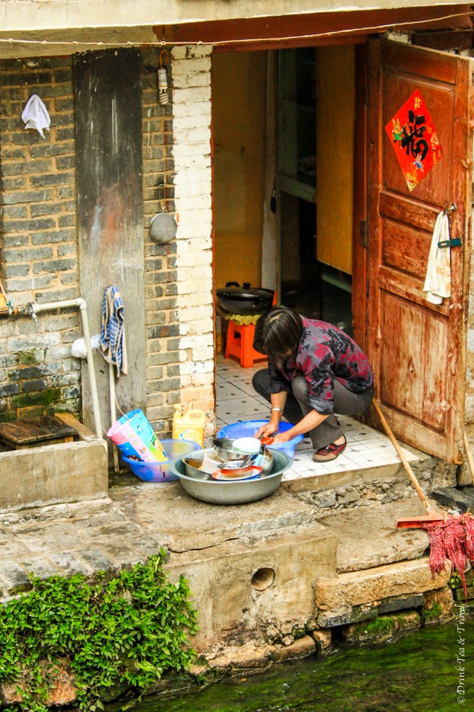Local woman doing the dishes outside of her home in Lijiang, China