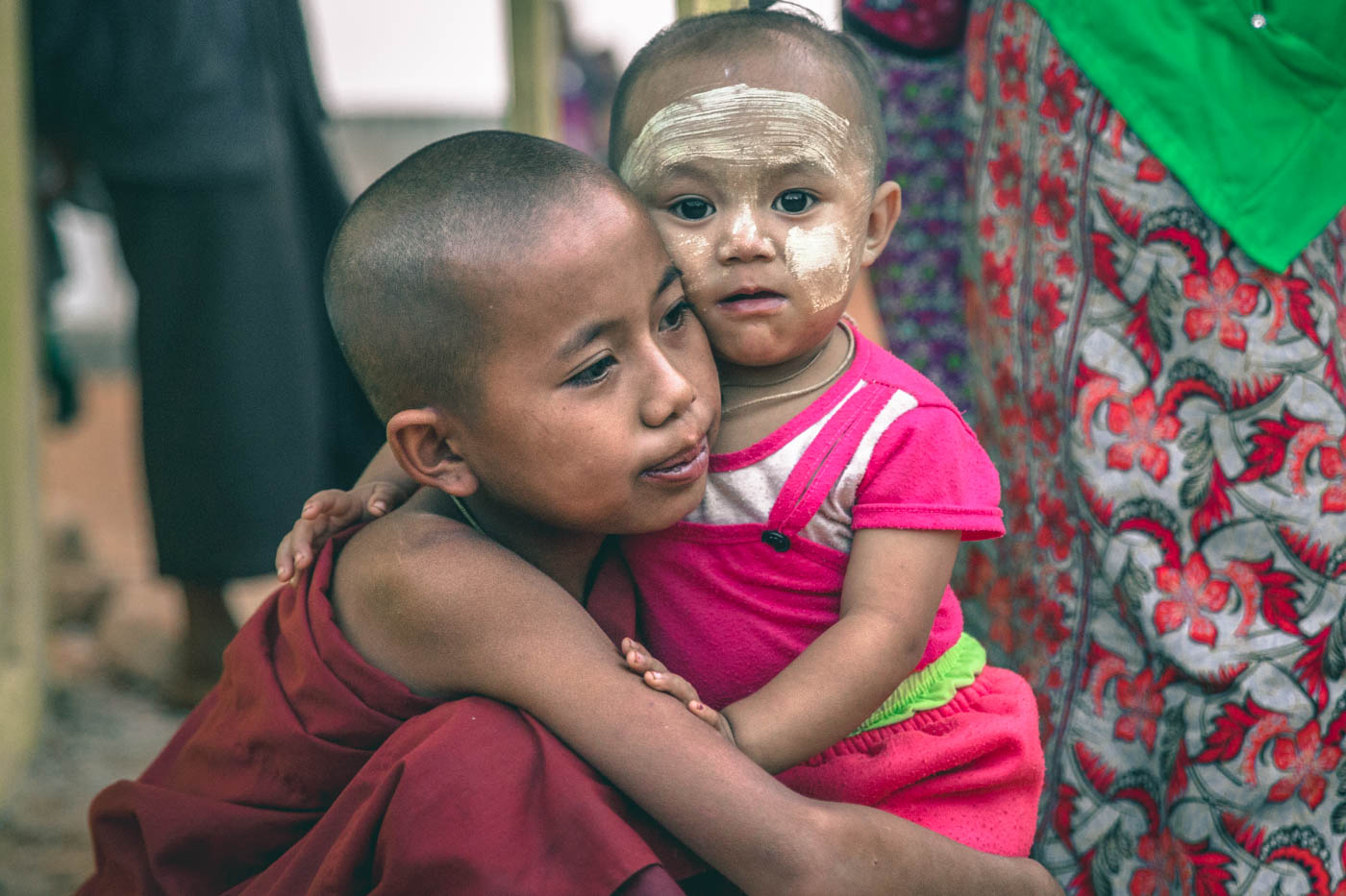 Novice monk hugs his baby sister in Myanmar.