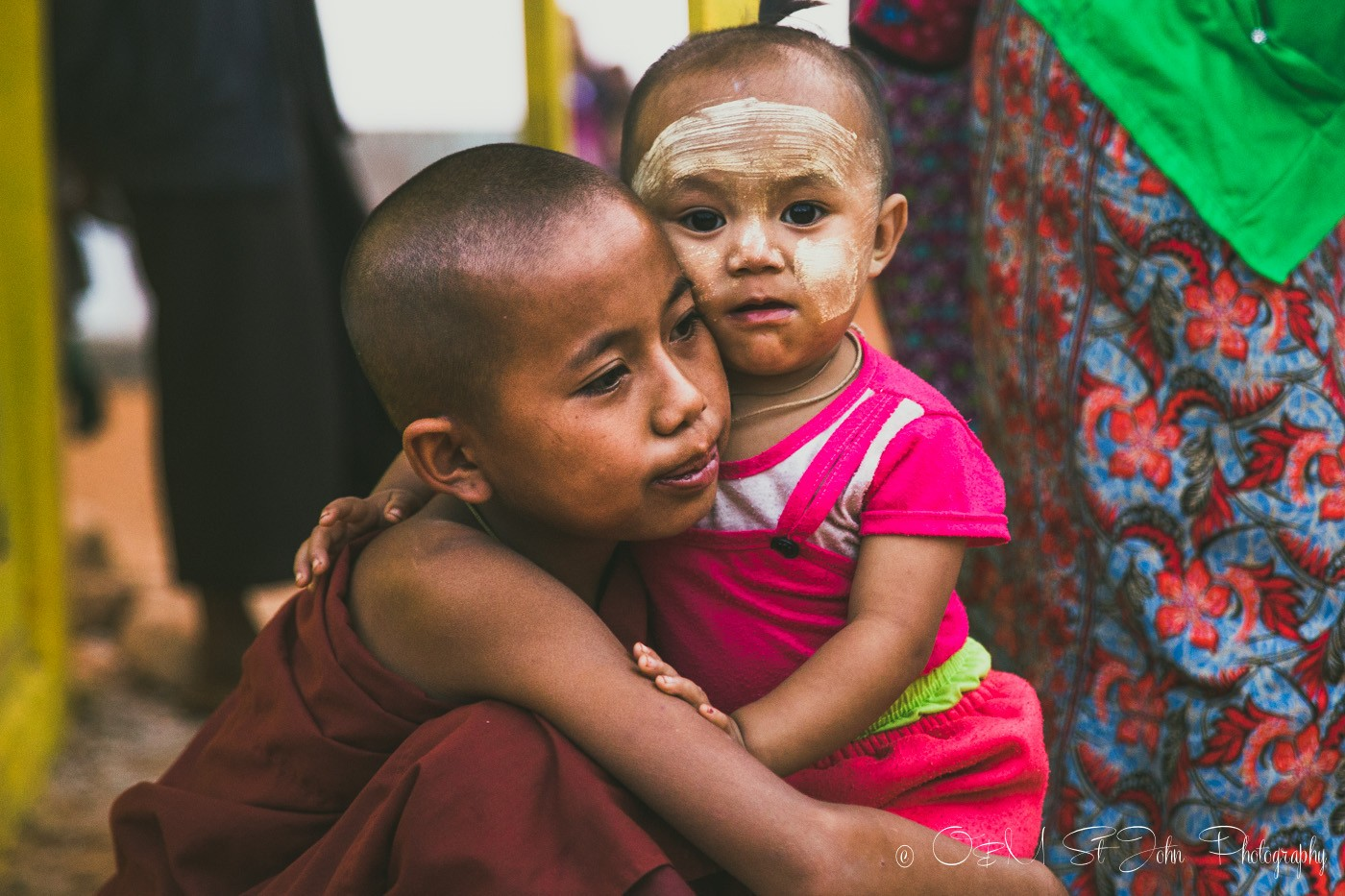 Young monk hugs their sibling at the Palaung Village Monk Harvest Festival