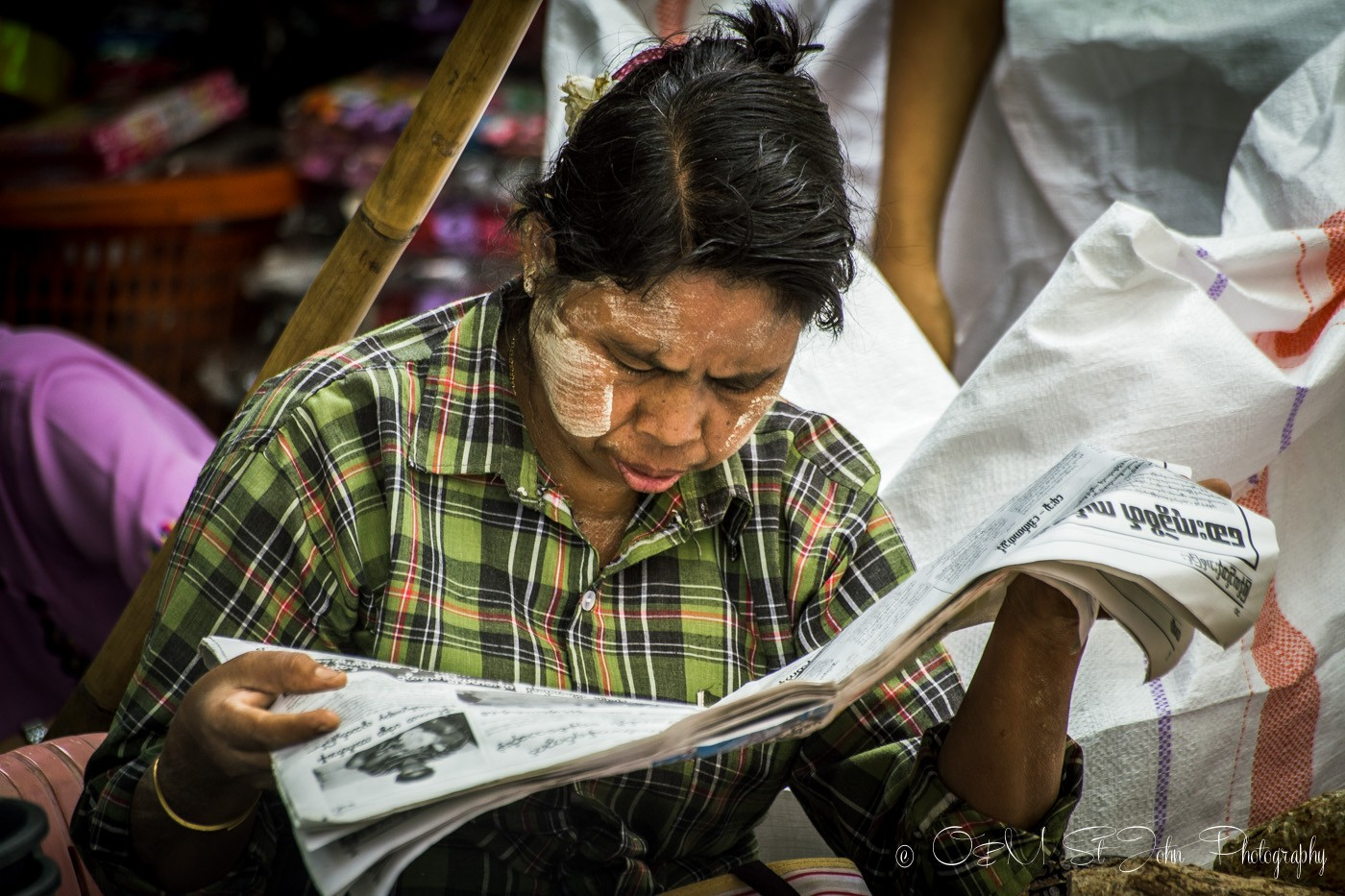 3 days in Yangon: Woman with thanaka paste on her cheeks is reading a local newspaper. Yangon, Myanmar