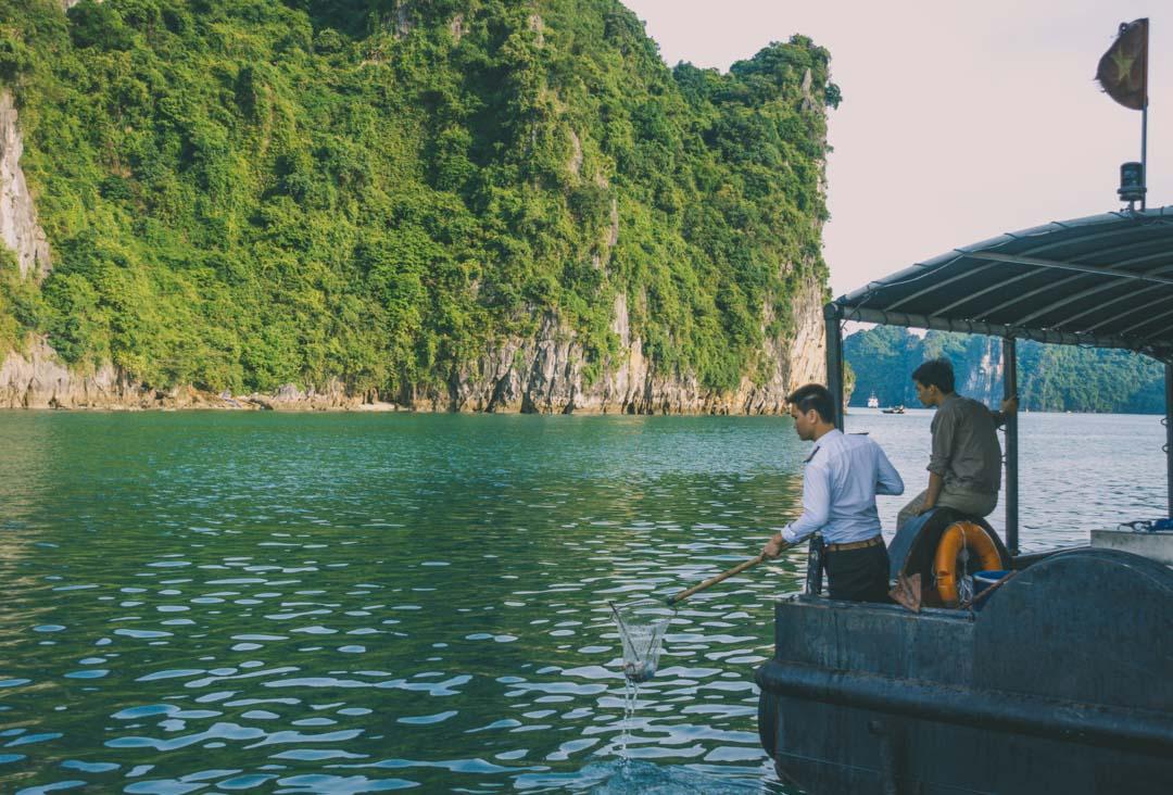 Halong Bay cruise. Indochina Junk - Dragon Legend staff collecting garbage at sea