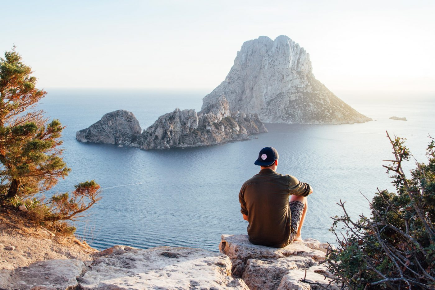 me time during a couples trip: man sitting on a rock overlooking the sea