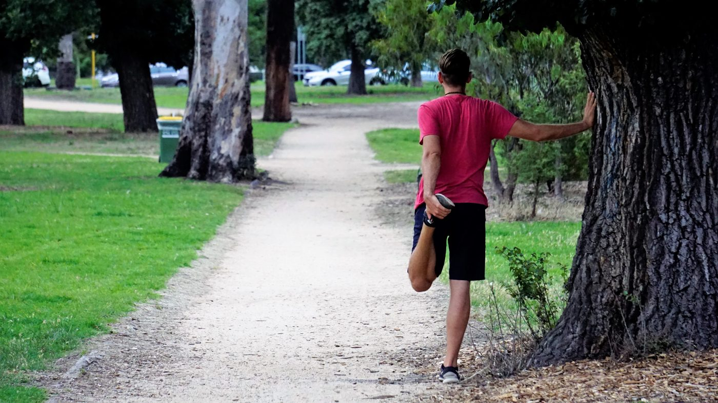 Staying Fit While Traveling: stretching by a tree