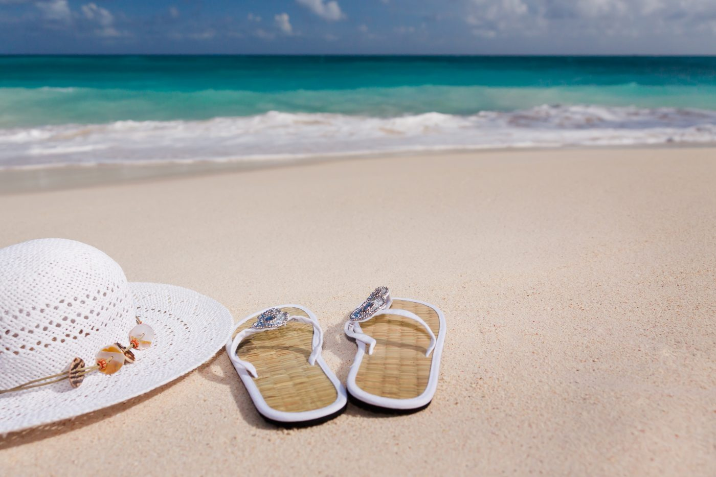 me time during a couples trip: sandals and hat on the beach